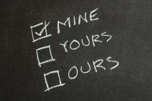"The words ""mine,"" ""yours,"" and ""ours,"" written on a chalkboard with a check mark next to ""mine."""