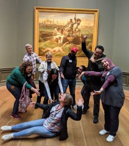 TCGers at the Museum Hack spree reenacting the event depicted in a painting on display.