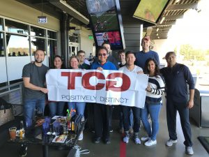 TCGers pose for a picture with the TCG banner at Top Golf.