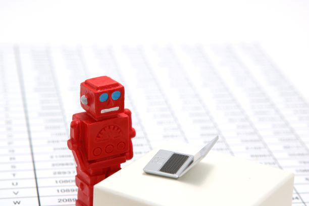 Robot figurine looking at a miniature laptop with an neutral face.