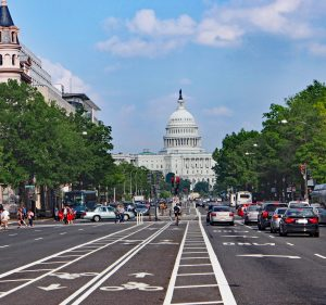 View of the street leading to capitol hill showing bike lanes and vehicles driving on the road.