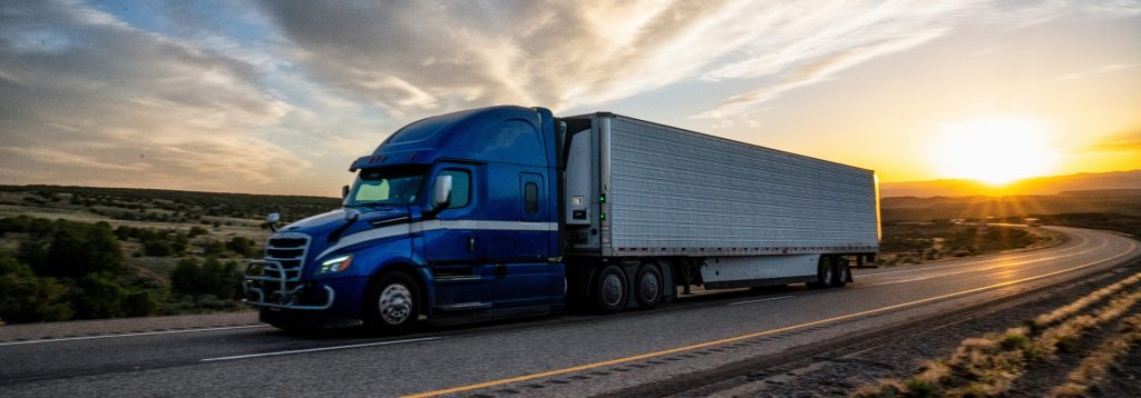 Tractor trailer driving during sunset.