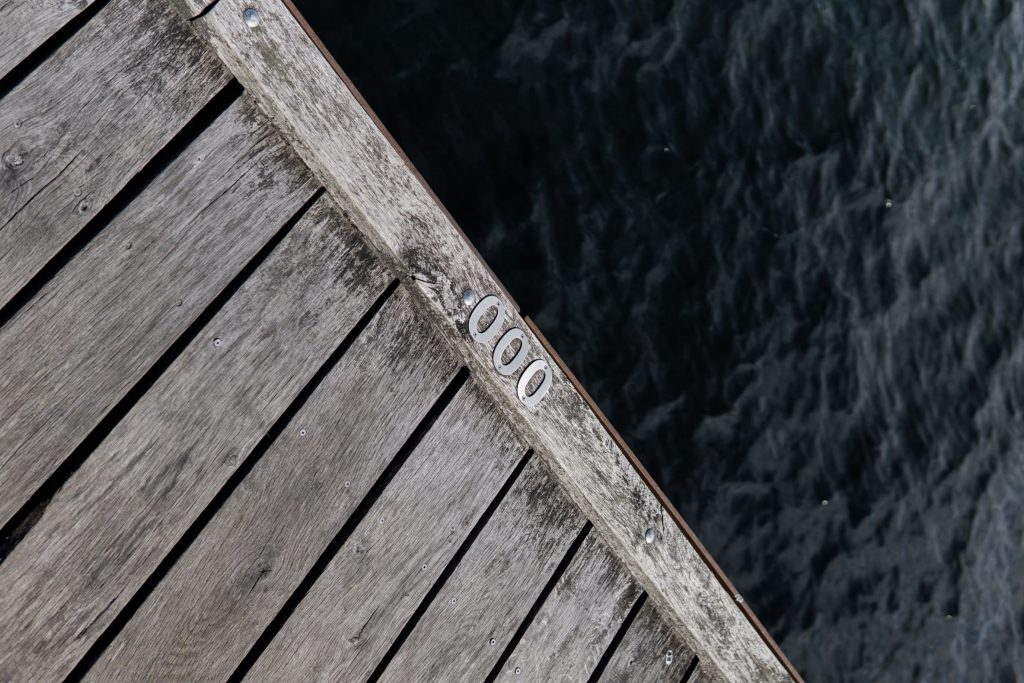 Metal numerals 000 nailed to a wooden dock. t